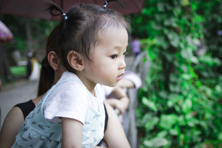 Side view of cute girl looking away in park
