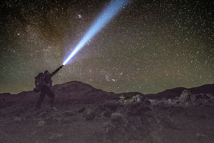 Hiker standing on mountain while pointing flashlight against galaxy at night