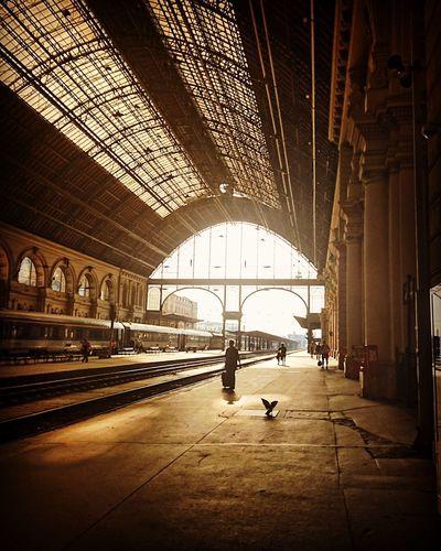 People walking on railroad station platform in city