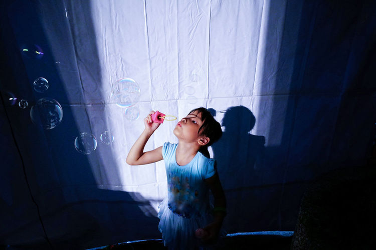 High angle view of girl blowing bubbles by white curtain