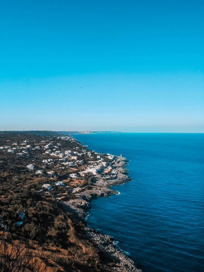 Aerial view of townscape by sea against clear blue sky