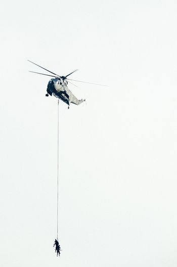 Low angle view of army soldiers hanging on rope attached to helicopter for rescue mission