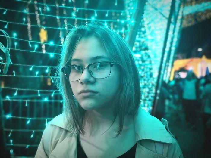 Portrait of teenage girl against illuminated lights at night