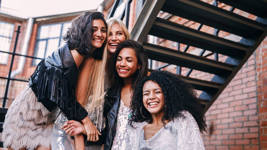 Low angle view of cheerful young female friends standing on staircase against building
