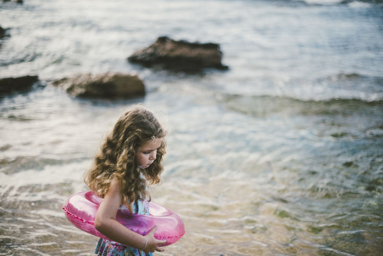 Girl with inflatable ring standing at beach