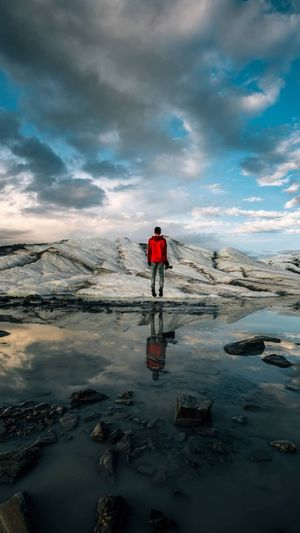 Rear view of man standing by ice formations against cloudy sky