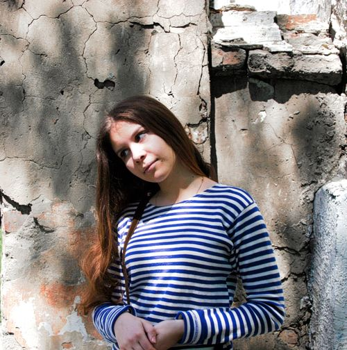 Thoughtful young woman with long hair standing against weathered wall