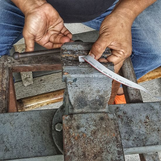 Midsection of man working on metal and cable