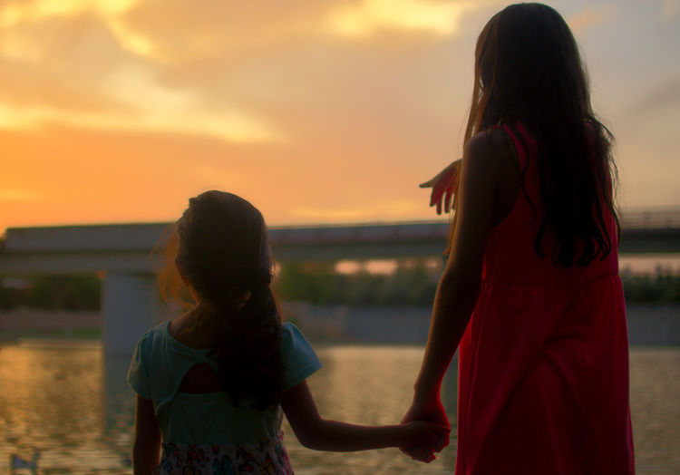 Bonding Childhood Girls Horizon Over Water Leisure Activity Lifestyles Long Hair Love Outdoors People Real People Rear View Sky Standing Sunset Three Quarter Length Togetherness Two People Water