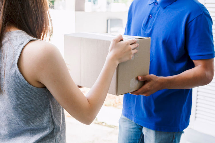 Woman accepting a delivery boxes from delivery man Delivery Adult Care Casual Clothing Communication Day Females Holding Indoors  Leisure Activity Lifestyles Men Midsection People Real People Rear View Standing Togetherness Two People Women Young Women