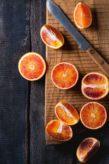 Sliced Sicilian Blood oranges fruits on wooden chopping board over dark wooden background. With vintage knife. Top view Black Background Sicilian Orange Blood Orange Bloody Orange Citrus Fruit Cutting Board Dark Photography Directly Above Food Food And Drink Freshness Fruit Healthy Eating Kitchen Knife Orange Orange - Fruit Orange Color Ripe SLICE Table Top View Of Food Wood - Material