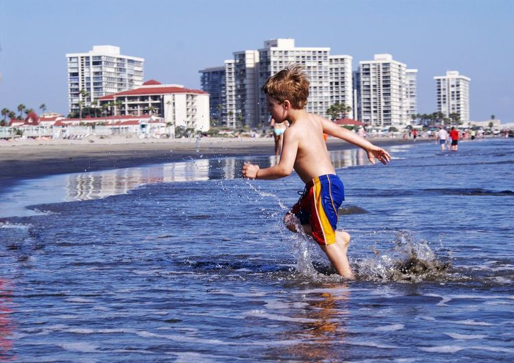 Side View Of Shirtless Boy Running At Beach Against Clear Sky
