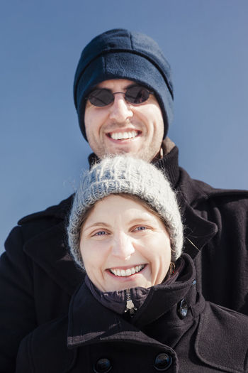 Low angle portrait of smiling couple wearing warm clothing against sky