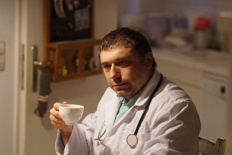 Thoughtful Mature Doctor With Coffee Sitting In Hospital