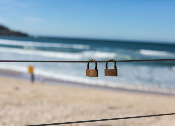 B Backgroundblur Depthoffield Foreground Focus Hanging No People Padlocks, Lovers Locks, Promises, True Love, Romance Sea Selective Focus Sky TwoIsBetterThanOne Water Two Is Better Than One