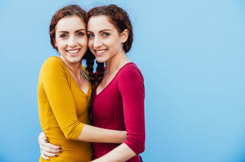 Portrait of smiling siblings against blue background