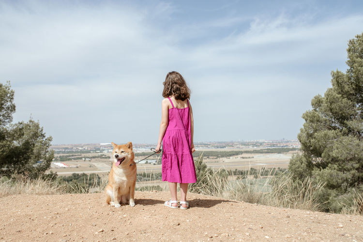 Rear view of woman with dog standing on land against sky