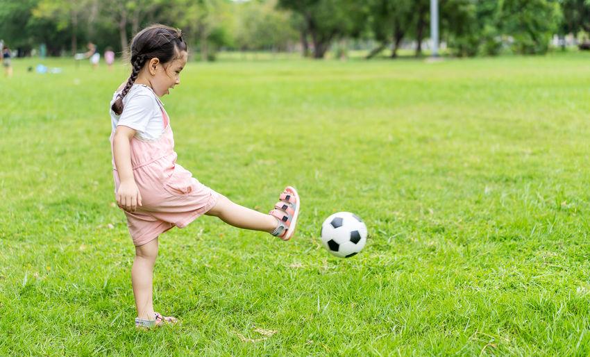 Full length of girl playing soccer on field