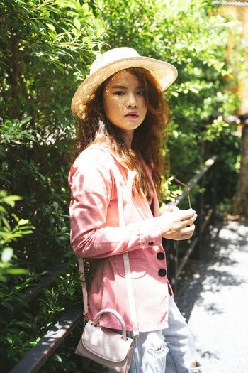 Portrait of young woman in hat standing against plants