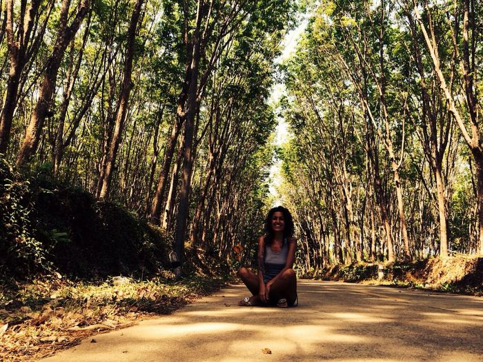 Happy woman sitting on dirt road amidst trees in forest