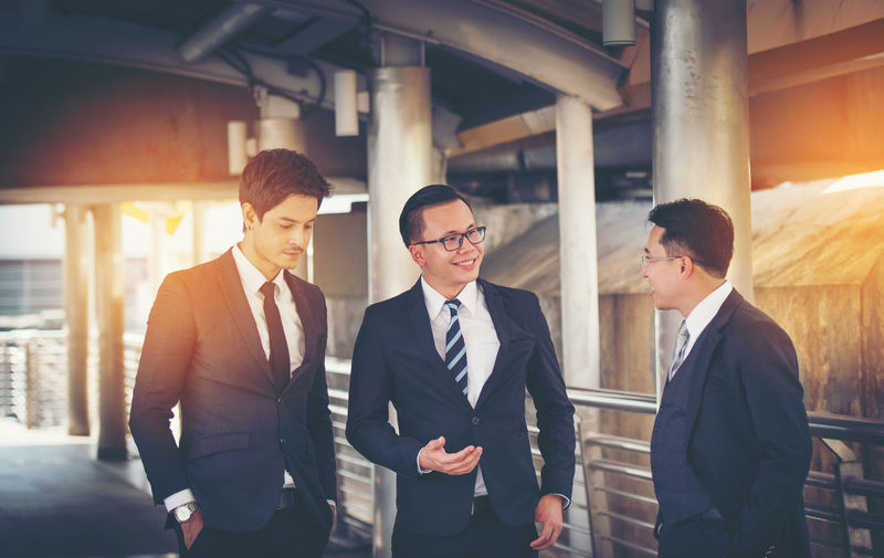 Business people work together confidently Adult Architecture Business Businessman Colleague Cooperation Corporate Business Day Eyeglasses  Friendship Indoors  Men Partnership - Teamwork People Real People Standing Suit Teamwork Togetherness Well-dressed Young Adult