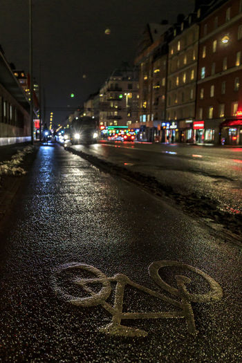 Winter cycling in Stockholm City Building Exterior Night Architecture Transportation Illuminated Street Built Structure Building Direction Road Car City Street Mode Of Transportation Motor Vehicle No People Communication The Way Forward Positive Emotion Text Neighborhood Place Bicycle Lane Wet Street