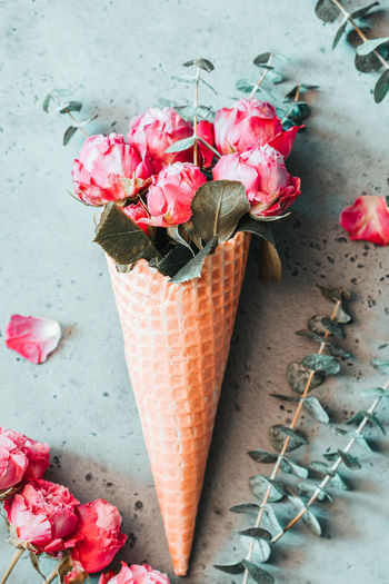 High angle view of pink roses in ice cream cone on table