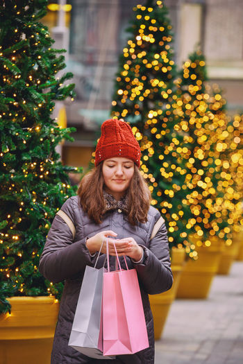 Young happy girl with shopping bags crossing a city street, colorful lights bokeh background Shopping Cart Shopping Mall Holiday Shopping Winter Shopping Xmas Shopping Christmas Shopping NYC Young Girl Young Girl Portrait NYC Street NYC LIFE ♥ Teenager Street Shopping Bag Customer  Street Multi Colored Mall Beautiful Happy Happy Time Happy New Year Christmas Holidays Christmas Holiday Shopping