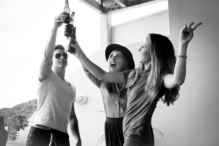 Friends Toasting Beer Bottles Against Wall