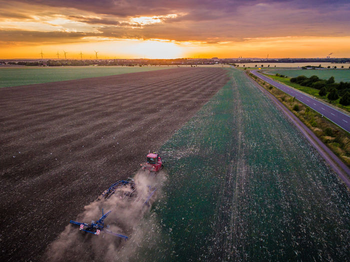 High Angle View Of Combine Harvester On Field Against Sky During Sunset
