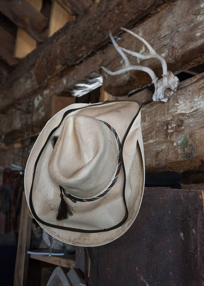Feb 2019 - Music Meadows Ranch Colorado Ranch Life Still Life Hat No People Close-up Wood - Material Focus On Foreground Old Antlers On Wall Log Cabin Barn Tack Room Low Angle View Built Structure Indoors  Wall Personal Accessory Clothing Day