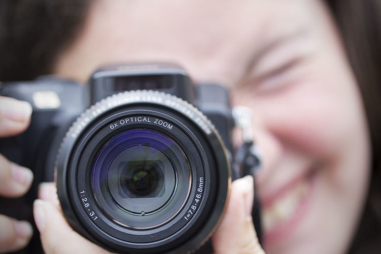 Close-up of smiling woman holding camera