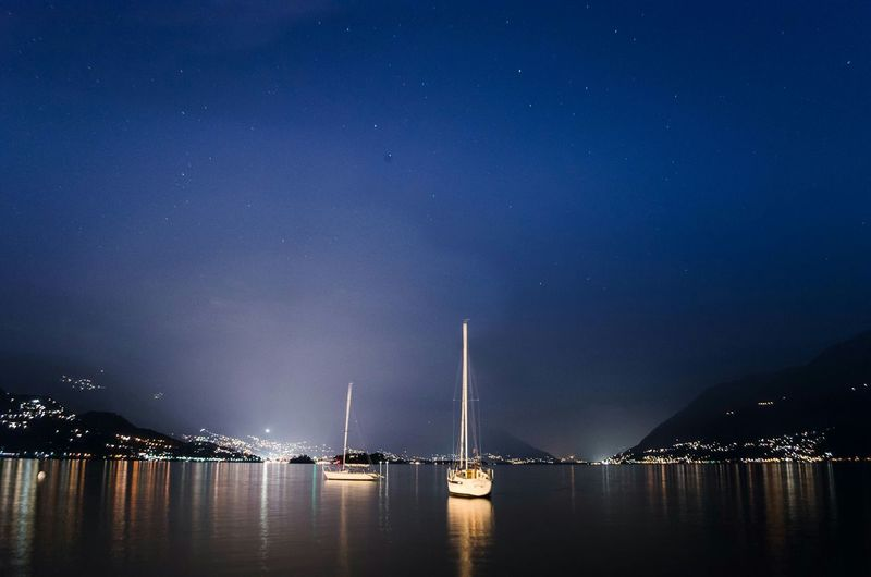 Sailboats Sailing In River Against Sky At Night