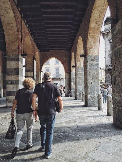 Rear View Of Man And Woman Walking Below Bridge