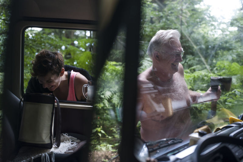Mid Adult Man Reflecting On Mirror While Senior Person Seen Through Windshield In Forest
