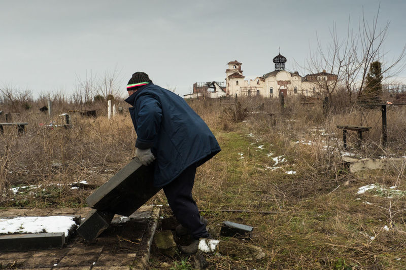 A local gravekeeper erects the grave stone that fell down during the fights in the area. Cemetary is located close to the Donetsk airport which was a place of very intense battles. The war in Donbas has since its start in March 2014 caused more than 10 000 casualties and displaced over 1 million of people. Caretaker DPR Damage Photojournalism Russia Ukraine Conflict Dnr Documentary Donbass Doneck Military Rebel Separatist Territory War