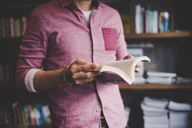 Midsection of man holding book