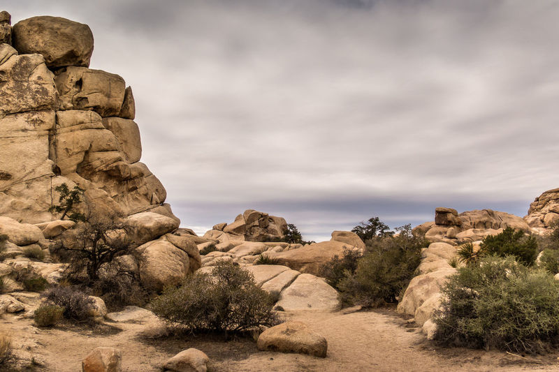 Rock formations on landscape against cloudy sky