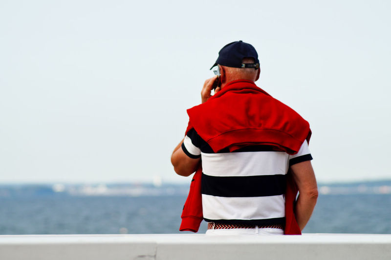 Rear view of man talking on phone while standing at railing against sea