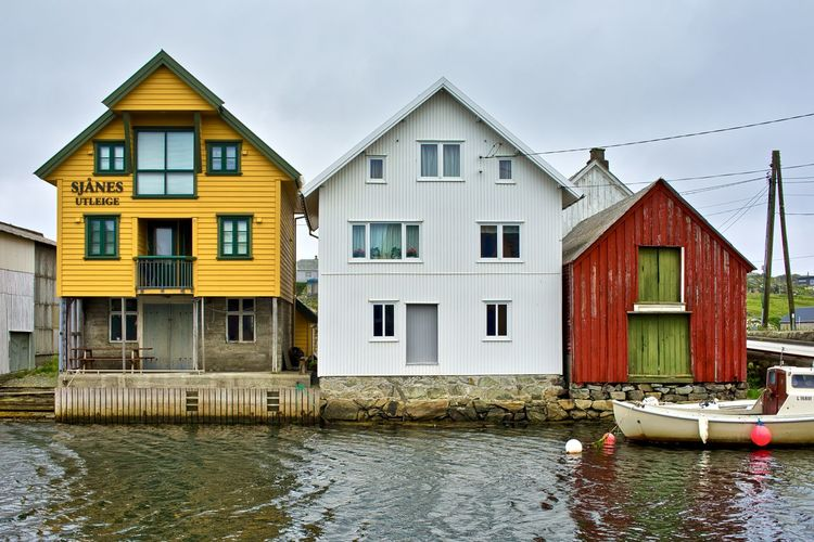 Norway, Utsira, Nordvik: wooden houses overlooking the water basin Body Of Water Wooden Cloudy Day Outdoors Horizontal Color Yellow Yellow Color Red Color Color Red Built Structure Building Exterior Architecture Water Nautical Vessel Waterfront Building Mode Of Transportation Transportation Nature Sky House Residential District No People Cloud - Sky River Window Row House