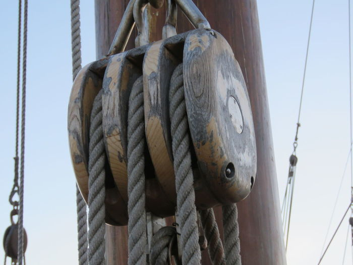 Low angle view of ropes on pulley by mast