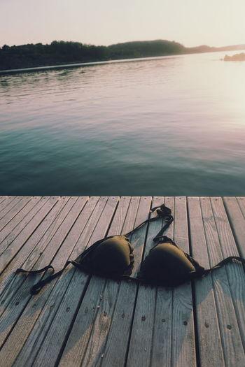 Bra on pier over lake during sunset