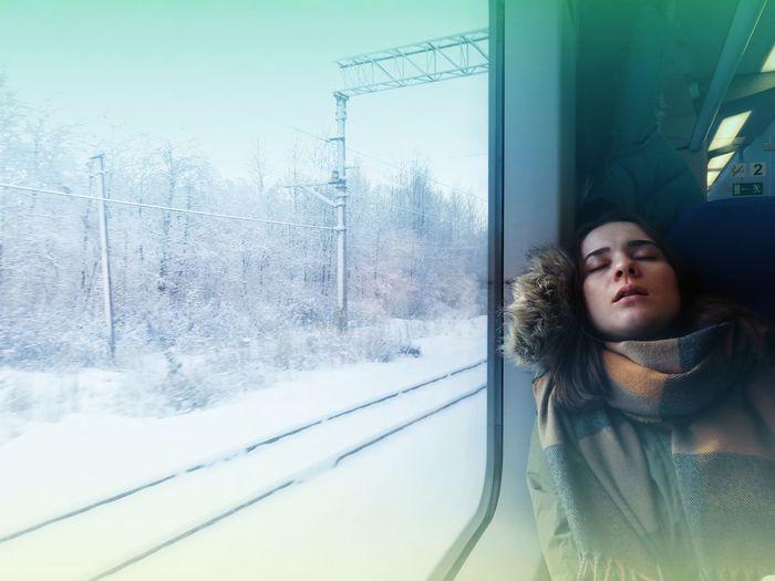 Young woman in train seen through window
