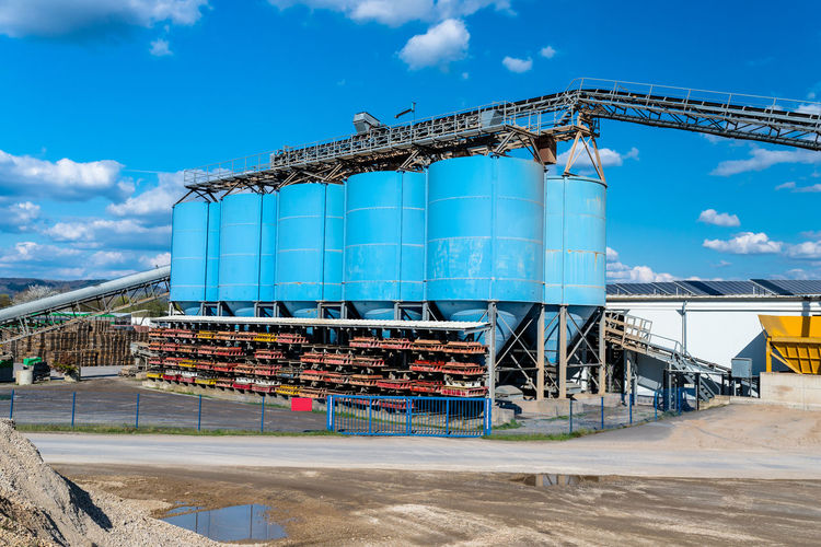 Big blue metallic industrial silos for the production of cement at an industrial cement plant