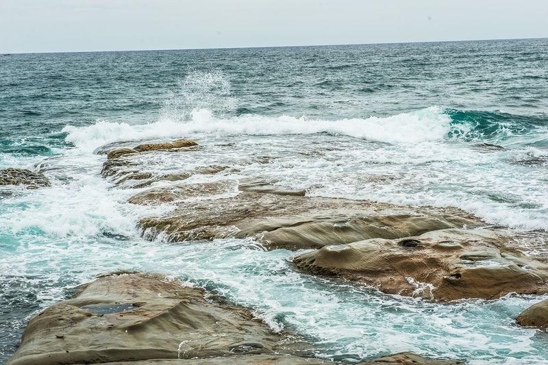 Scenic view of sea waves splashing on shore
