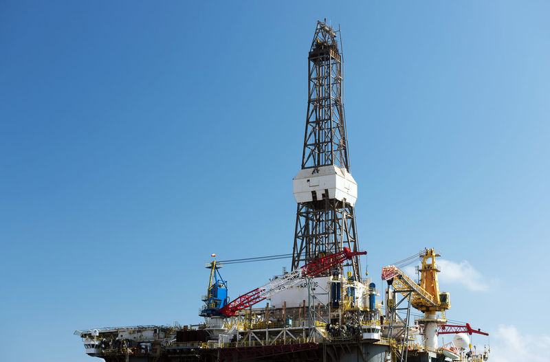 Low Angle View Of Oil Rig Against Blue Sky