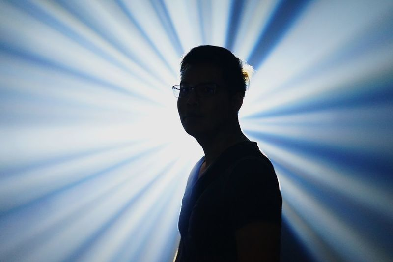 Young man standing against light beams