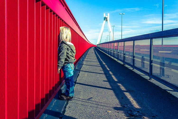 Girl standing by railing of bridge