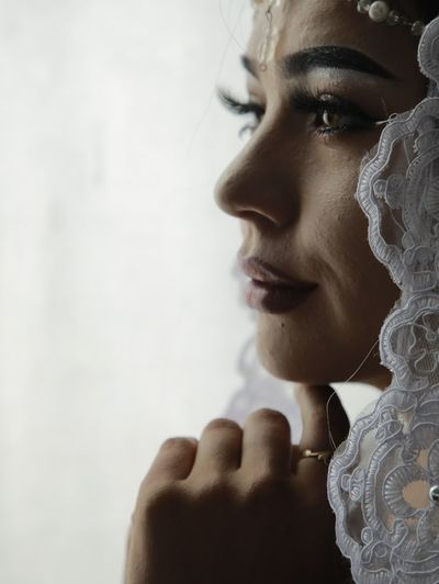 Close-up of bride against white background
