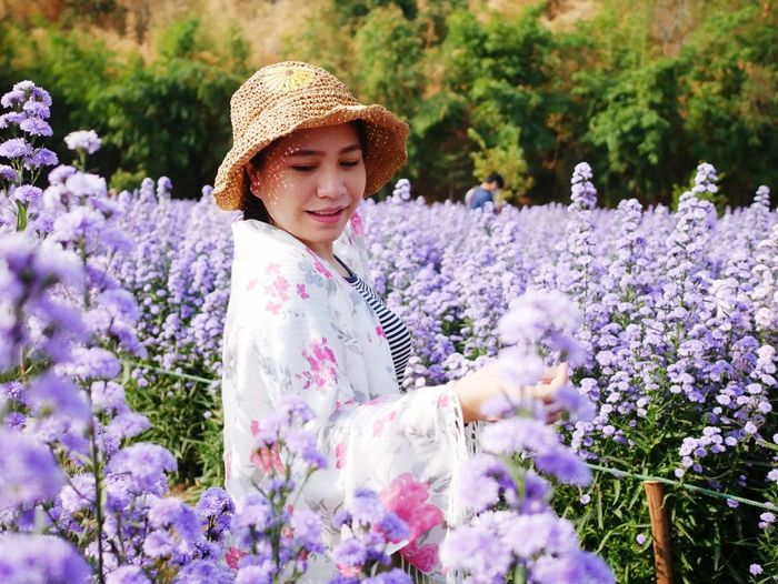 Beautiful woman standing by purple flowering plants